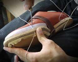 出し縫いを手作業で行う職人(ハンドソーンウェルト製法)